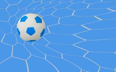 Biało niebieska piłka w siatce bramkarskiej niebieskie tło
