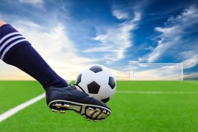Boisko do piłki nożnej noga kopiąca piłkę do bramki