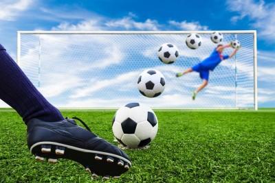 Piłka lecąca do bramki, noga kopiąca piłkę, bramkarz, bramka, trawa
