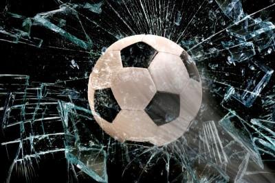 piłka przebijająca szkło/lód czarne tło, piłka nożna
