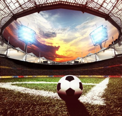 Piłka na rogu boiska rzut rożny stadion trawa światła trybuny kibice pomarańczowe niebo