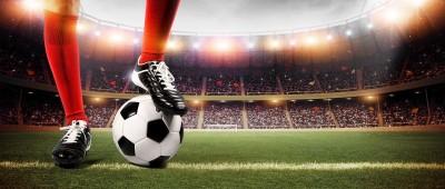 Nogi piłkarza na piłce stadion piłka nożna czerwony strój trybuny kibice