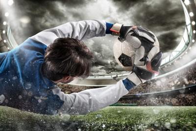 Broniący piłkarz we wodzie piłka nożna noc bramka stadion kibice