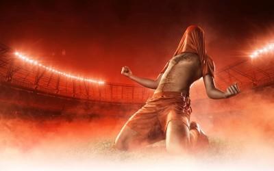 Zadowolony piłkarz z koszulką na głowie czerwony strój tło dym stadion