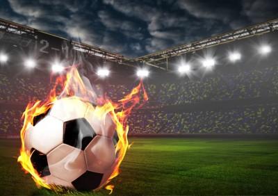 Płonąca piłka na boisku kibice trybuny piłka nożna