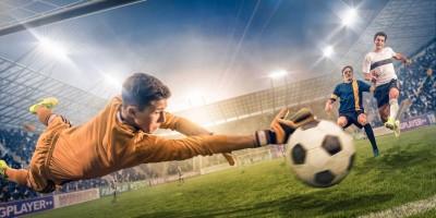 Bramkarz broniący piłka lecąca do bramki piłkarze piłka nożna boisko stadion kibice światła