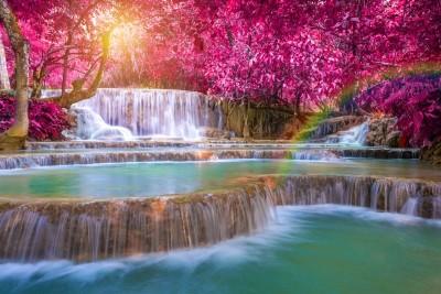 Wodospad z tęczą, fioletowymi drzewami i przebijającym słońcem