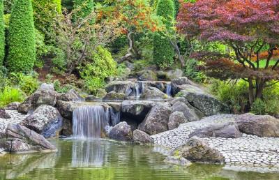 Mały wodospad z kamieniami, zielonymi i fioletowymi drzewami
