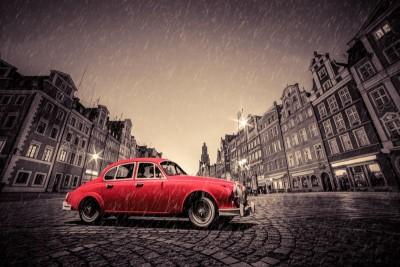 Czerwony samochód szare budynki plac ulica deszcz burza
