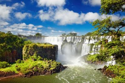 Wodospad  z unoszącą sie parą zielone drzewa i niebo